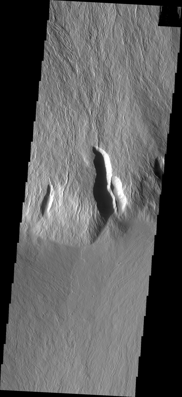 This image captured by NASA's 2001 Mars Odyssey spacecraft shows the steep escarpment between Olympus Mons and the surrounding volcanic plains.