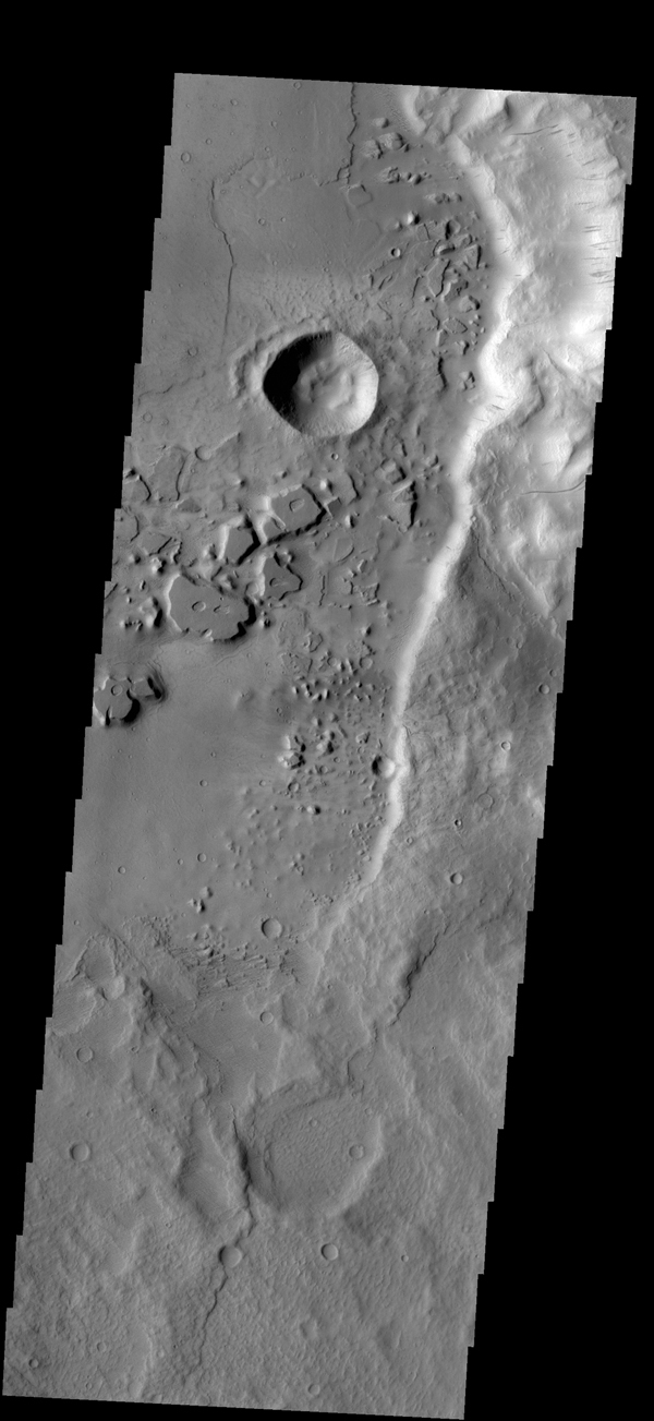 Dark streaks mark the steep slopes of this ridge located east of Mangala Valles as seen by NASA's 2001 Mars Odyssey spacecraft.