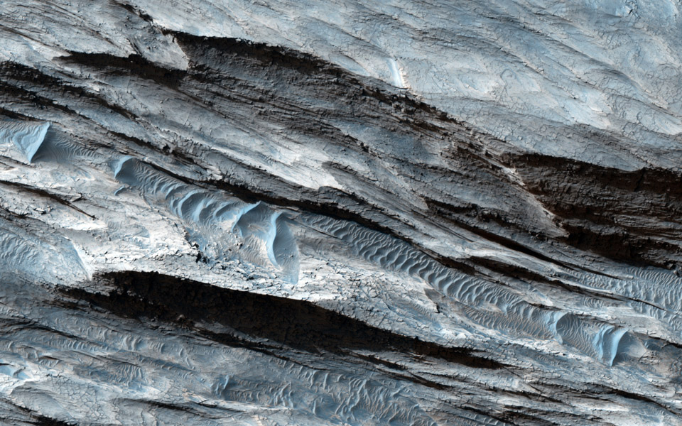 This basin in Ceti Mensa, as seen by by NASA's Mars Reconnaissance Orbiter, exposes concentric rings in the sedimentary layers. Dark sand ripples and textures in the bedrock suggesting wind scouring are also apparent.