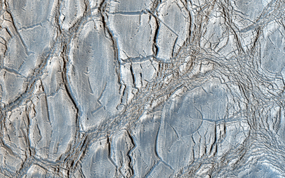 With its cracked, blistery appearance, this mound near the center of a very large, over 5-kilometer diameter mid-latitude crater poses an interesting question: how did this form? This image is from NASA's Mars Reconnaissance Orbiter.