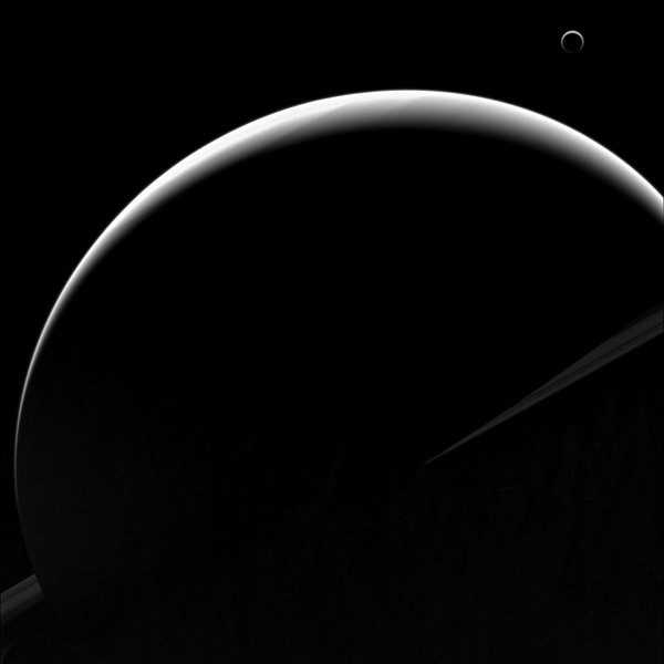 The View From Nasas Cassini Orbiter Shows Titans Crescent Nearly Encircling Saturns Disk Due To The