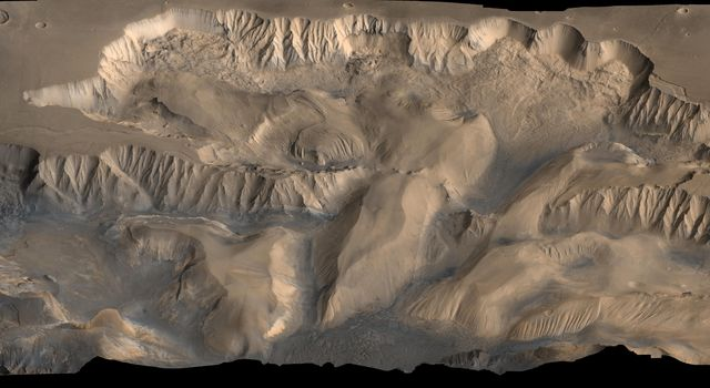 An oblique, color image of central Valles Marineris, Mars showing relief of Ophir and Candor Chasmata; view toward north. The photograph is a composite of Viking high-resolution images in black and white and low-resolution images in color.