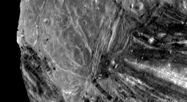 This image of the Uranian moon, Miranda, was taken Jan 24, 1986 by NASA's Voyager 2. This image reveals a bewildering variety of fractures, grooves and craters, as well as features of different albedos (reflectancea).