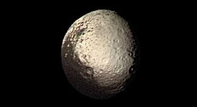 Saturn's outermost large moon, Iapetus, has a bright, heavily cratered icy terrain and a dark terrain, as shown in this NASA Voyager 2 image taken on Aug. 22, 1981.