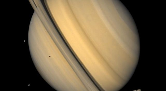 This approximate natural-color image from NASA's Voyager 2 shows Saturn, its rings, and four of its icy satellites. Three satellites Tethys, Dione, and Rhea are visible against the darkness of space.