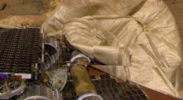 This image from the Imager for Mars Pathfinder (IMP) camera shows the rear part of NASA's Sojourner rover, the rolled-up rear ramp, and portions of the partially deflated airbags.