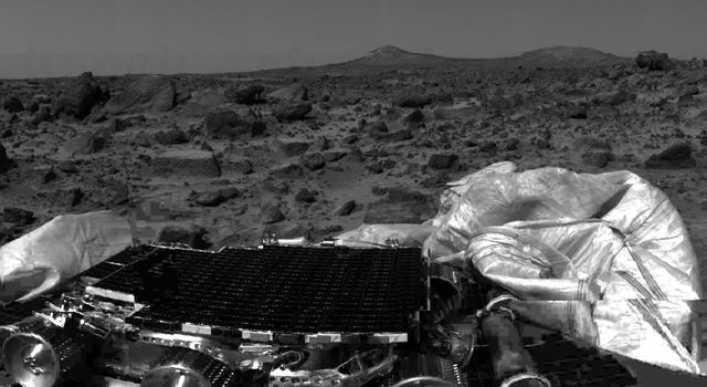 NASA's undeployed Sojourner rover is seen still latched to a lander petal in this image, taken on July 4, 1997, the lander's first day on Mars. Portions of a petal and deflated airbag are in the foreground.
