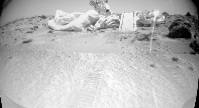 Taken from NASA's Mars rover Sojourner's forward camera, this image features a rover's-eye view of the Sagan Memorial Station; Sojourner's tracks are shown leading away from the spacecraft.