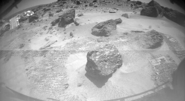 One of NASA's Sojourner's two front cameras took this image of the Sagan Memorial Station on Sol 6. The lander and its deployed rear ramp are at upper left, while several large rocks appear at center.