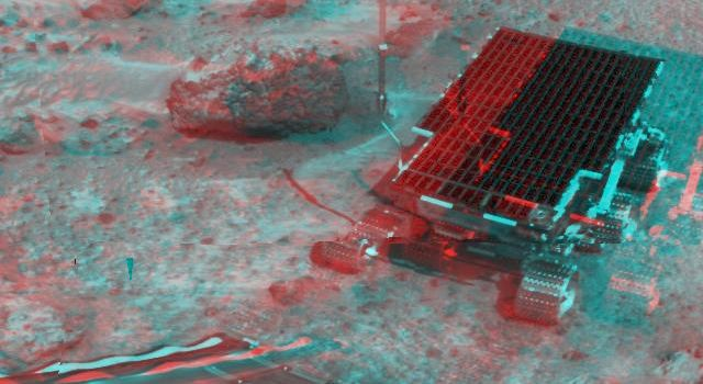 At right, NASA's Sojourner has traveled off the lander's rear ramp and onto the surface of Mars. The rock 'Barnacle Bill' and the rear ramp is to the left of Sojourner. 3-D glasses are necessary to identify surface detail.