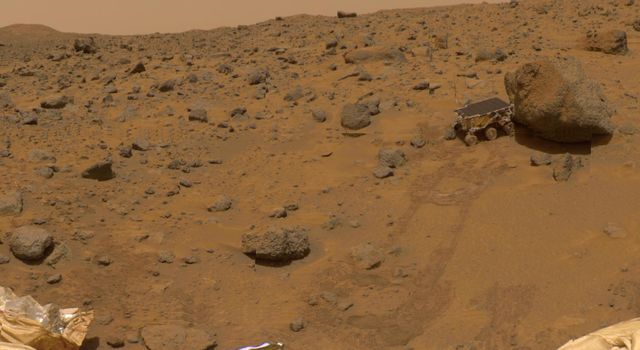 This portion of the 360-degree gallery panorama shows NASA's Pathfinder's rear ramp, the rock 'Barnacle Bill' at left, and leading up to the large rock 'Yogi' are the rover's tracks.