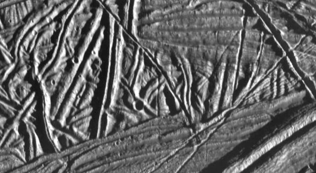 This high resolution image of the icy crust of Europa, one of Jupiter's moons, reveals a surface criss-crossed by multiple sets of ridges and fractures. This image was taken by NASA's Galileo spacecraft on February 20, 1997.