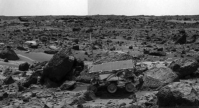 NASA's Sojourner rover's Alpha Proton X-ray Spectrometer (APXS) is shown deployed against the rock 'Moe' on the afternoon of Sol 64 (September 7, 1977). The rocks to the left of Moe are 'Shark' (left of Sojourner) and 'Half Dome' (behind Sojourner).