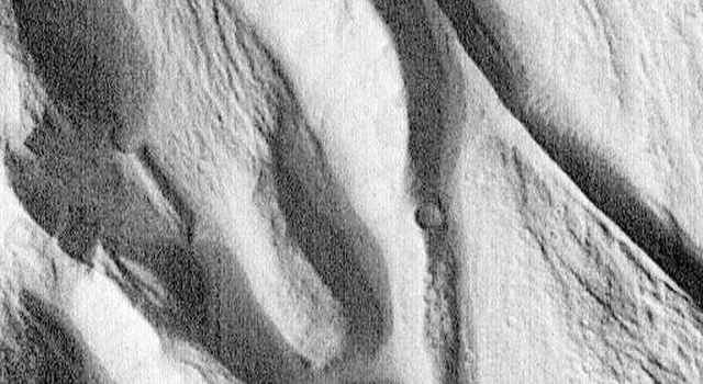 Complex floor deposits showing a  landscape of ridges and troughs within Western Ganges Chasma, Valles Marineris are evident in this image taken by NASA's Mars Global Surveyor.