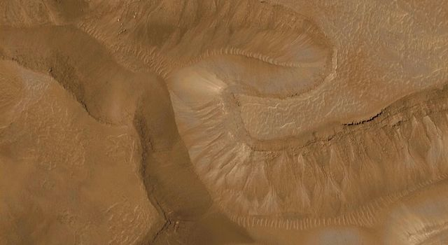 A series of troughs and layered mesas in the Gorgonum Chaos region on Mars are evident in this image taken by NASA's Mars Global Surveyor.