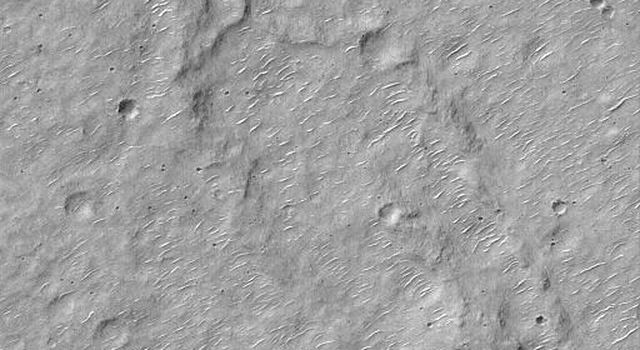 These images captured by NASA's Mars Global Surveyor show a ridged and cratered plain in southern Hesperia Planum on left, and  a layered northeastern wall of a meteor impact crater in Noachis Terra on right.