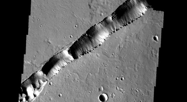 This large fracture occurs on the lava flows of Ceraunius Tholus on Mars, taken by NASA's Mars 2001 Odyssey spacecraft.