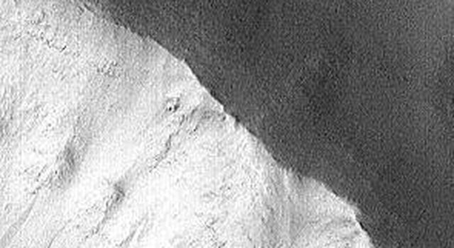 This image of a moderately small impact crater on Mars was taken by the Mars Global Surveyor Orbiter Camera (MOC) on October 17, 1997. Long, linear features of different brightness values are seen on the steep slopes inside and outside the crater.