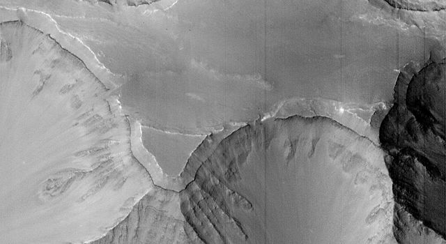 NASA's Mars Global Surveyor acquired this image of the Martian surface in the early evening of January 1, 1998. Shown here are a plateau and surrounding steep slopes within the Valles Marineris.