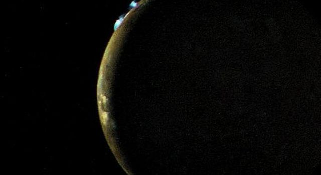 Voyager 2 took this picture of Io on the evening of July 9, 1979, from a range of 1.2 million kilometers. On the limb of Io are two blue volcanic eruption plumes about 100 kilometers high.
