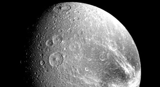 Many large impact craters are seen in this view of the Saturnian moon Dione taken by NASA's Voyager 1 on Nov. 12, 1980 from a range of about 240,000 kilometers (149,000 miles).