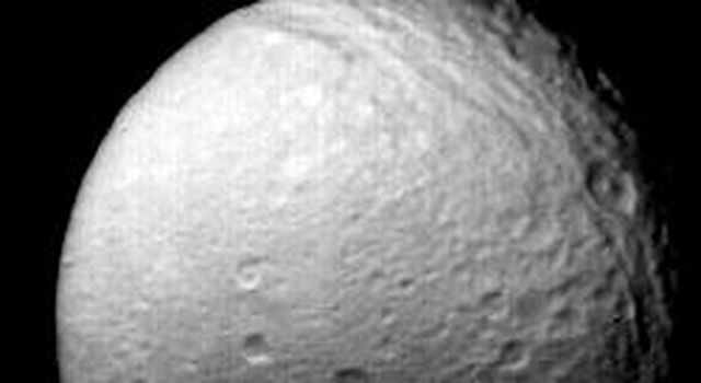 NASA's Voyager 2 obtained this view of Saturn's moon Tethys on Aug.25, 1981, from a distance of 540,000 kilometers (335,000 miles). It shows the numerous impact craters and fault valleys of a very ancient surface.
