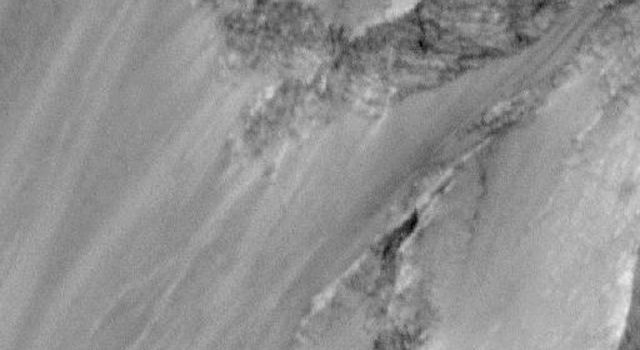 NASA's Mars Global Surveyor acquired this image on Jan 6, 1998. Shown here are layered materials in the walls and on the floors of the enormous Valles Marineris system.