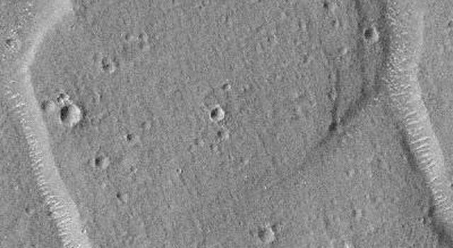 This image taken on August 31, 1998 by NASA's Mars Global Surveyor shows the floors of polygon troughs that have bright, almost evenly spaced, windblown ripples or drifts.
