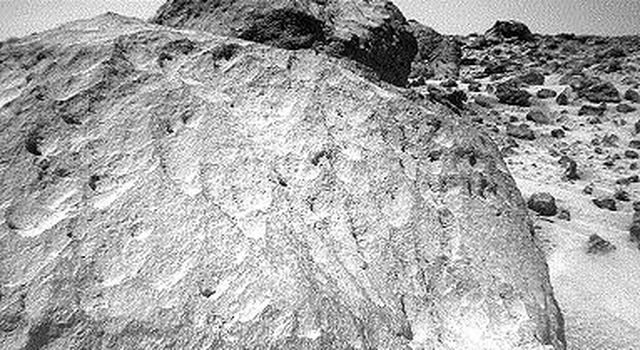 A close-up view of the rock 'Moe' in the 'Rock Garden' at the Pathfinder landing site. 'Moe' is a meter-size boulder that, as seen by NASA's Sojourner, has a relatively smooth yet pitted texture upon close examination. Sol 1 began on July 4, 1997.