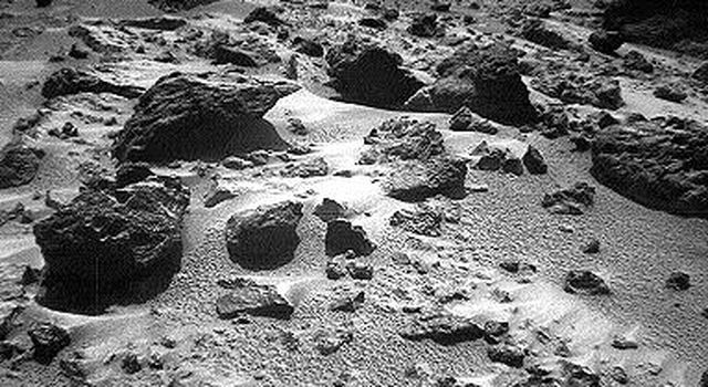 This right image of a stereo image pair, taken on Sol 72 (September 15) from NASA's Sojourner rover's front cameras, shows areas of the Pathfinder landing site never before seen. The large rock on the right is 'Chimp.' Sol 1 began on July 4, 1997.