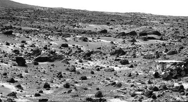 This image taken on the morning of Sol 80 (September 23, 1997) shows NASA's Sojourner rover with its Alpha Proton X-ray Spectrometer (APXS) deployed against the rock 'Chimp.' On the left horizon is the rim of 'Big Crater,' 2.2 km away.