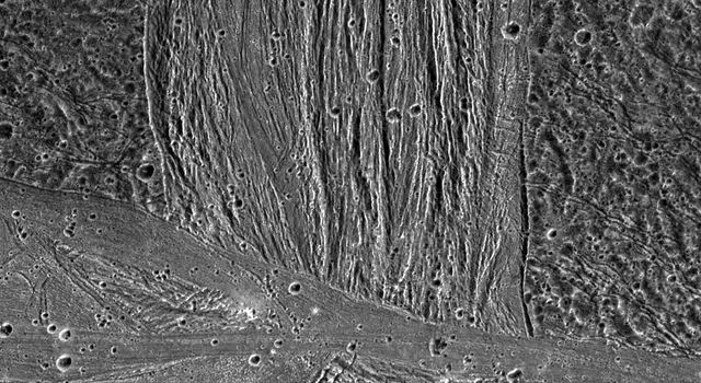 A swath of grooved terrain named Erech Sulcus cuts north-south across the ancient dark terrain of Marius Regio. Mosaic images were taken by the Solid State Imaging (SSI) system on NASA's Galileo spacecraft.