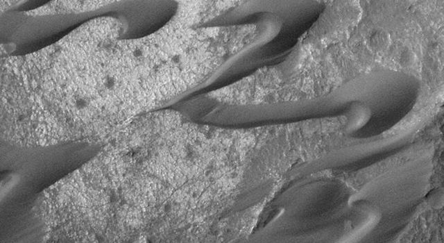 This dramatic image was NASA's Mars Global Surveyor captured during March 1999 shows a field of dark sand dunes in the Nili Patera region of Syrtis Major on Mars. The shapes of these dunes indicate that wind has been steadily transporting the dark sand.