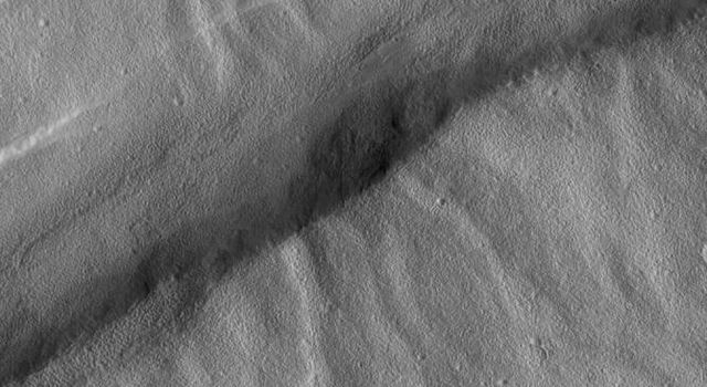 NASA's Mars Global Surveyor shows valleys on the northwest flank of Alba Patera Volcano which are old and have been cut by younger faults that created graben.