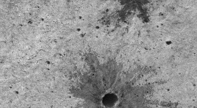 NASA's Mars Global Surveyor shows  two excellent examples of small impact craters on the martian surface. Each has a dark-toned deposit of material that was blown out of the crater (called ejected) during the impact.
