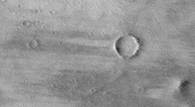 NASA's Mars Global Surveyor shows Daedalia Planum, a broad, wind-swept volcanic plain on Mars. A combination of bright surfaces (where sand and/or dust has accumulated) and dark surfaces (where sand and/or dust has been removed) are seen.