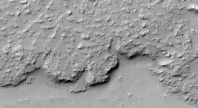 NASA's Mars Global Surveyor shows the margin of a large lava flow located on Daedalia Planum, southwest of the Arsia Mons volcano. The lava flow surface is rough but mantled with fine sand or dust.