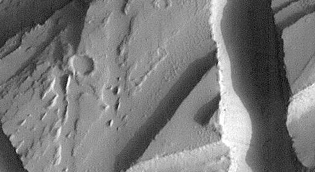 NASA's Mars Global Surveyor shows a collection of troughs and depressions located in northern Tharsis known as the Olympica Fossae, south of the Alba Patera volcano.