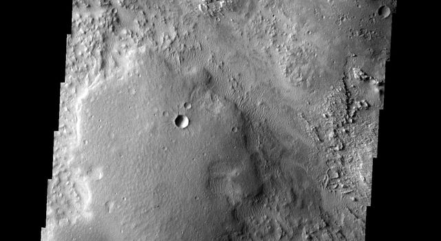 The wind is eroding some of the materials in this region more readily than others, indicating a complex surface history on Mars. This image was taken by NASA's Mars 2001 Odyssey spacecraft.