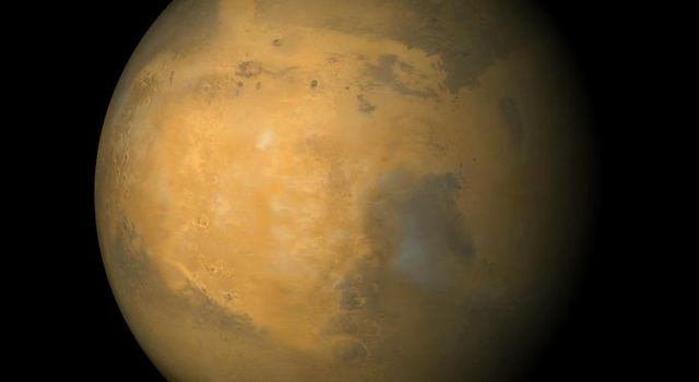 NASA's Mars Global Surveyor shows a large, circular bright region called Arabia Terra. Syrtis Major is the dark region toward the lower right. The north polar cap is visible at the top, and the bright feature lower right is the Hellas Basin.
