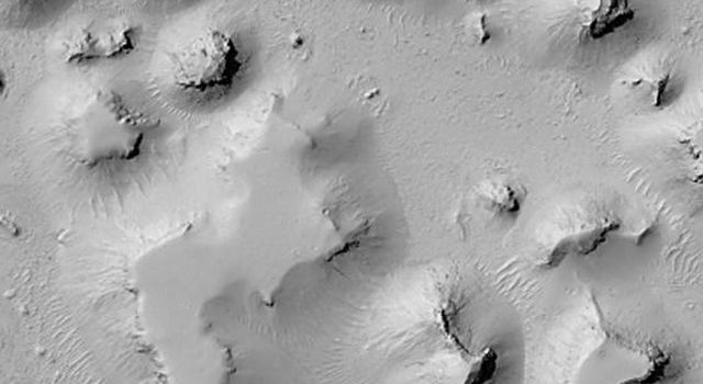 NASA's Mars Global Surveyor shows mesas and smaller buttes that occur on the Elysium Plains, south of the Cerberus region in the Martian eastern hemisphere.
