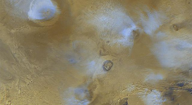 NASA's Mars Global Surveyor shows the volcanoes of the Tharsis region on Mars. The white or bluish-white features are clouds. Clouds are common over the larger Tharsis volcanoes in mid-afternoon.