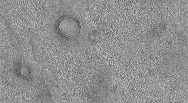 NASA's Mars Global Surveyor shows northern plains of Mars exhibit craters that often appear to be partly buried by or exhumed from beneath layers of pitted and eroded material.