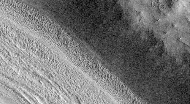 NASA's Mars Global Surveyor shows valley floors in the middle latitudes of Mars, particularly in the 'fretted terrain' of northern Arabia Terra which have curious grooved and pitted surfaces.