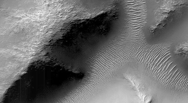 NASA's Mars Global Surveyor shows small valleys in the martian cratered highlands are often quite old and have been modified by erosion and wind action. The valleys shown here are located on a crater rim in Terra Tyrrhena.