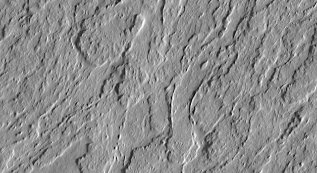 NASA's Mars Global Surveyor shows the lower south flank of the Olympus Mons volcano on Mars; lava flows with leveed central channels and a variety of surface textures are present. The picture was taken in July 1998.