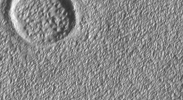NASA's Mars Global Surveyor shows lava flows and channels on the flanks of the Alba Patera volcano on Mars, mostly obscured by a covering of eroded, lumpy-textured material of unknown origin. This picture was taken in July 1998.