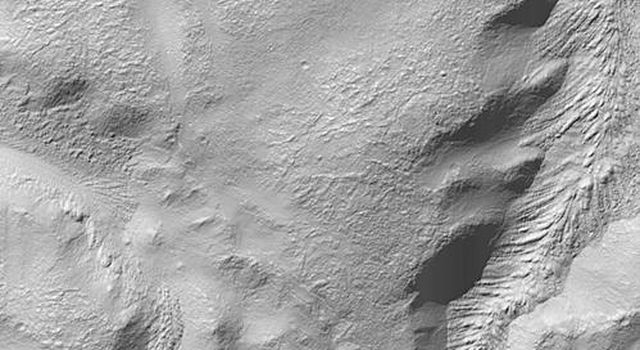 NASA's Mars Global Surveyor shows the wall of a 72 kilometer-wide (45 mile-wide) impact crater in Promethei Terra on Mars. Its inner walls appear to be deeply gullied.