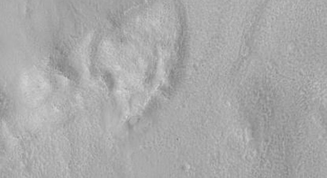 NASA's Mars Global Surveyor shows the eastern third of an impact crater located in Acidalia Planitia on Mars featuring the walls, raised rim, and ejecta material thrown out of the crater during this blast.