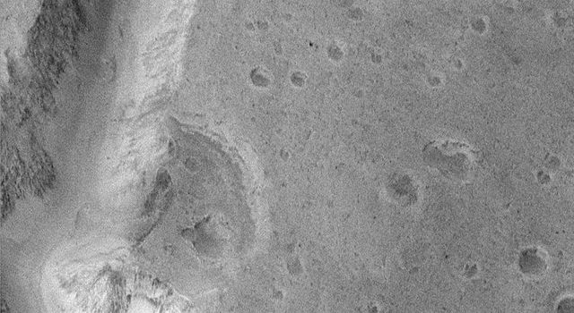 NASA's Mars Global Surveyor shows a transition zone between the cratered highlands of Arabia Terra, and the less-cratered lowlands of Acidalia Planitia on Mars. Boulders are present on some hill slopes, and plains between the hills are rough and pitted.